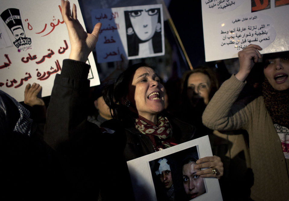 "Egyptian woman activists chant slogans while taking part in a protest  against sexual harassment and against the Islamist dominated Shura Council blaming women for the attacks against them, in Cairo, Egypt, Tuesday, Feb. 12, 2013. Arabic in the background reads ""The revolution will go through the bodies of women not over them."" (AP Photo/Nasser Nasser)"