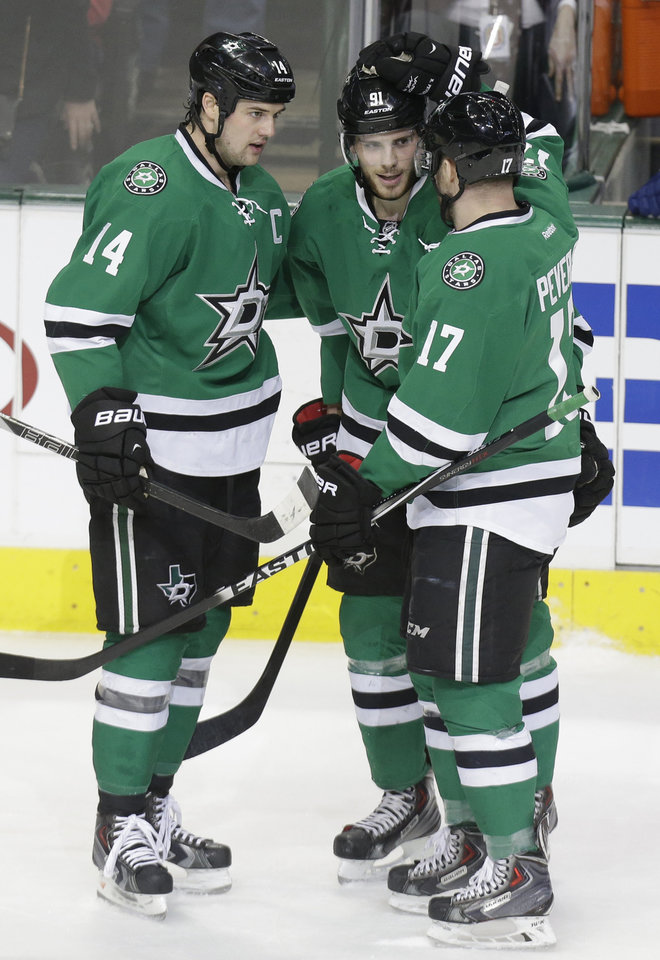 Photo - Dallas Stars Tyler Seguin, center, is congratulated by teammates Jamie Benn (14) and Rich Peverley (17) after Seguin scored his second goal against  the Vancouver Canucks during the first period of an NHL hockey game Thursday, March 6, 2014, in Dallas. (AP Photo/LM Otero)