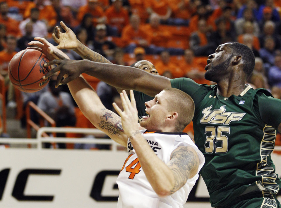 Oklahoma State forward Philip Jurick (44) grabs a rebound in front of South Florida center Jordan Omogbehin (35) in the second half of an NCAA college basketball game in Stillwater, Okla., Wednesday, Dec. 5, 2012. (AP Photo/Sue Ogrocki)