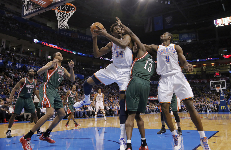 Oklahoma City\'s Hasheem Thabeet (34) pulls in a rebound over Milwaukee \'s Ekpe Udoh (13) during the season finally NBA basketball game between the Oklahoma City Thunder and the Milwaukee Bucks at Chesapeake Energy Arena on Wednesday, April 17, 2013, in Oklahoma City, Okla. Photo by Chris Landsberger, The Oklahoman