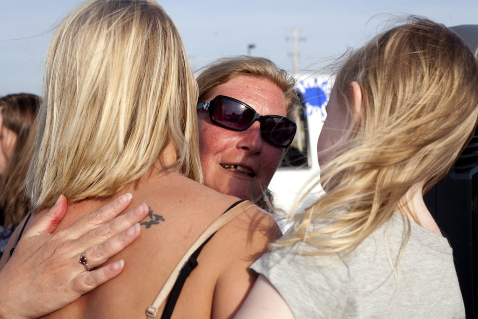 Photo - Shelly Heeringa, mother of 25-year-old Jessica Heeringa embraces Amanda, left, and Alivia Brown during a vigil for her daughter on Tuesday, April 30, 2013 at Pointes Mall in Norton Shores, Mich. Jessica Heeringa was allegedly abducted at about 11 p.m. on Friday, April 26, 2013 from the Exxon Mobil gas station at 1196 E. Sternberg Road, where she worked as a night clerk. Hundreds gathered at the mall, close to where Heeringa worked, to light candles, show support to her family, and pray for her well being. (AP Photo/The Muskegon Chronicle, Jon Garcia) ALL LOCAL TV OUT; LOCAL TV INTERNET OUT