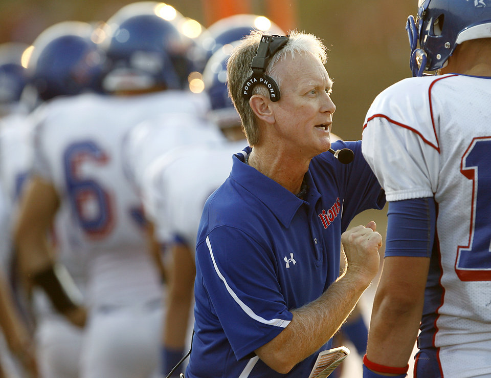 Photo - Moore coach Scott Myers talks with quarterback Corey Reeves during their game against Westmoore during their high school football game at Moore Stadium in Moore, Oklahoma on Friday, September 2, 2011. Photo by John Clanton, The Oklahoman