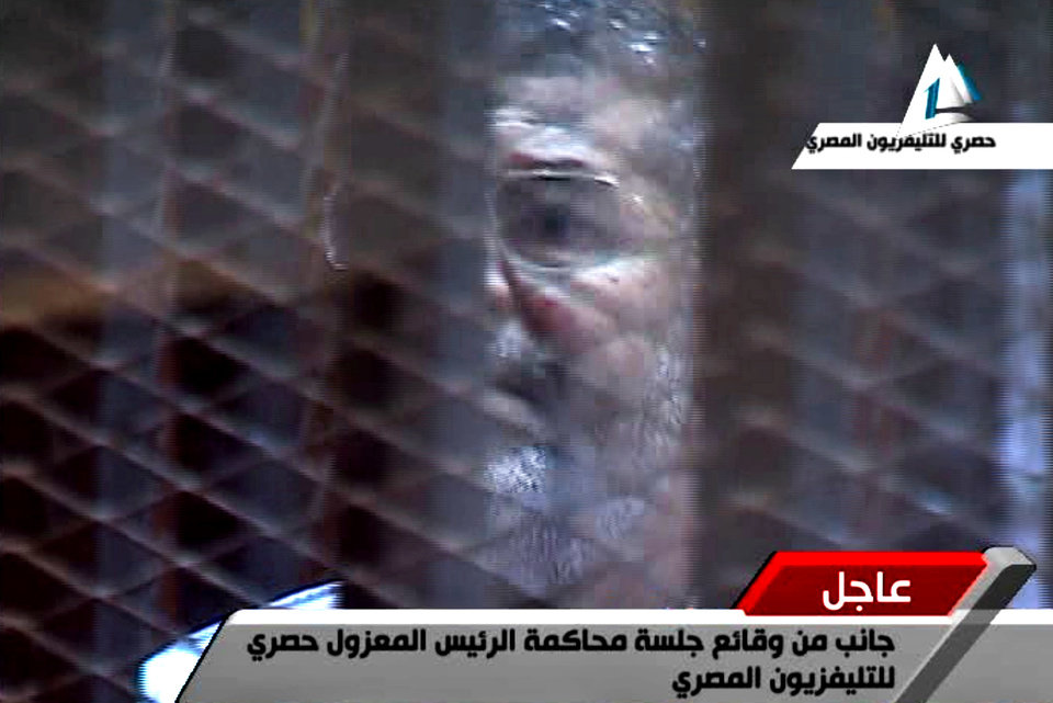 Photo - In this image taken from Egypt State TV,  Egypt's toppled President Mohammed Morsi stands inside a glass-encased metal cage in a courtroom in Cairo, Egypt, Tuesday, Jan. 28. 2014. Morsi was separated from other defendants for the start of a new trial Tuesday over charges from prison breaks during the country's 2011 revolution, state television reported. (AP Photo/Egyptian State TV)