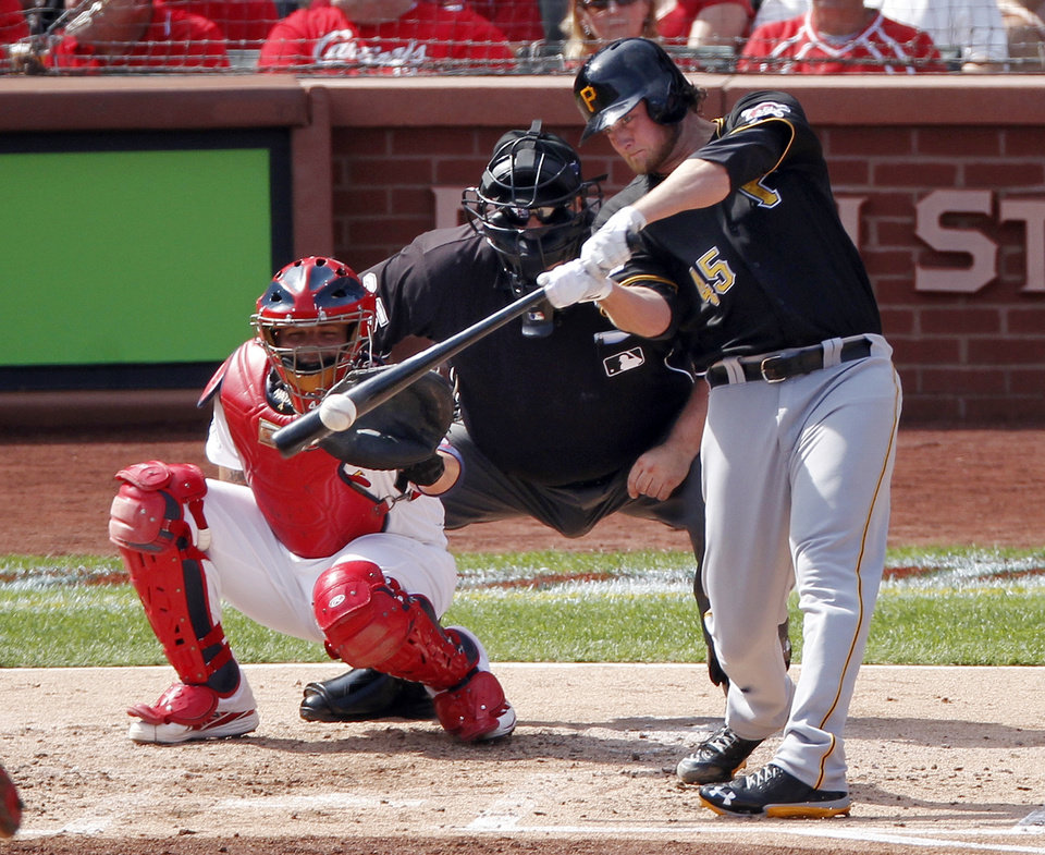 Pittsburgh Pirates pitcher Gerrit Cole (45) hits an RBI single against the St. Louis Cardinals in the second inning of Game 2 of baseball's National League division series on Friday, Oct. 4, 2013, in St. Louis. Catching for the Cardinals is Yadier Molina. (AP Photo/Sarah Conard)