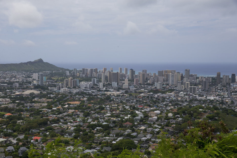 Photo - The city of Honolulu can be seen from Round Top Dr, Saturday, Aug. 9, 2014 in Honolulu.  Despite the rains and winds from Tropical Storm Iselle that pounded the state Friday, Hawaii will hold primary elections today.  (AP Photo/Marco Garcia)