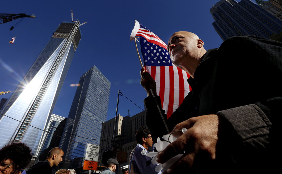 Marcio Rodriguez holds a United States flag as he pays respects in front of the construction site of One World Trade Center during the 11th anniversary of the Sept. 11 terrorist attacks, Tuesday, Sept. 11, 2012, in New York. (AP Photo/Julio Cortez)