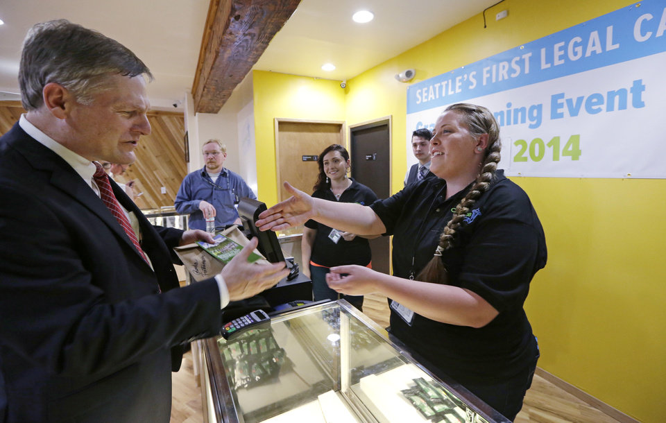 Photo - Seattle City Attorney Pete Holmes, left, shakes hands with clerk Pam Fenstermacher after purchasing marijuana at Cannabis City, Tuesday, July 8, 2014, in Seattle, on the first day that sales of recreational pot became legal in the state.  Washington on Tuesday became the second state to allow people to buy marijuana legally in the U.S. without a doctor's note as eager customers who lined up outside stores made their purchases and savored the moment. (AP Photo/Elaine Thompson, Pool)