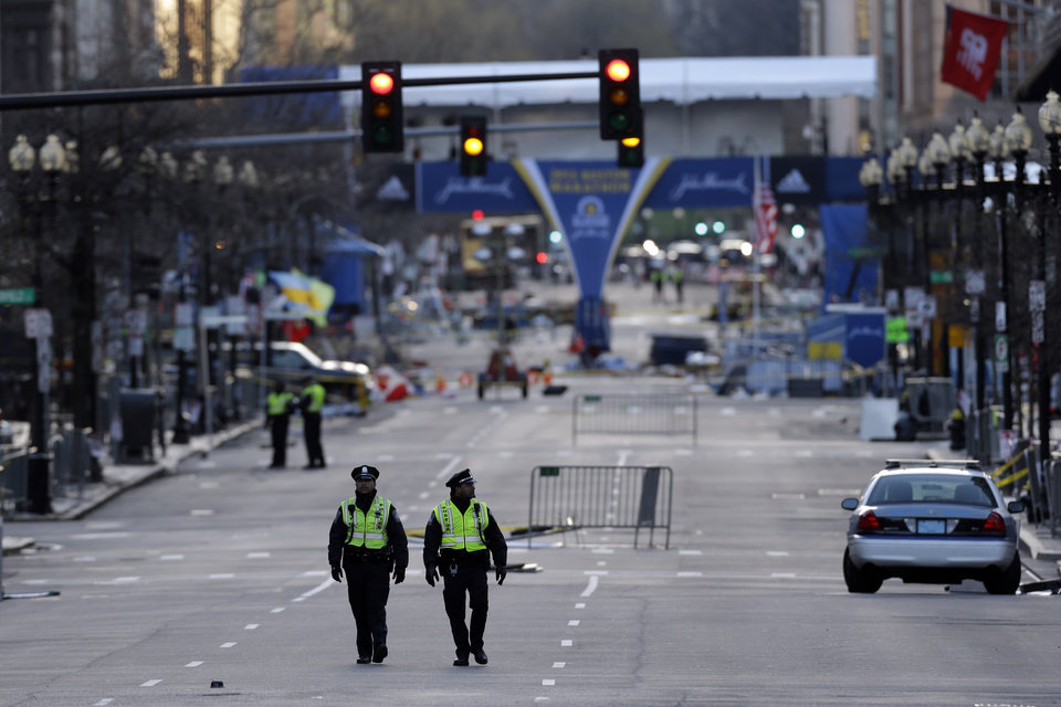 Police officers walk on Boylston Street near the finish line of Monday\'s Boston Marathon explosions, which killed at least three and injured more than 140, Thursday, April 18, 2013, in Boston. (AP Photo/Matt Rourke)
