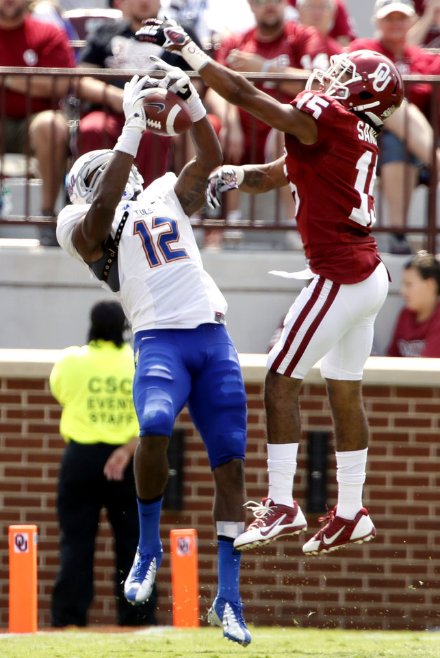 Photo - Tulsa's Jordan James (12) makes a catch defended by Oklahoma's Zack Sanchez (15) during the second half of a college football game between the University of Oklahoma Sooners (OU) and the Tulsa Golden Hurricane (TU) at Gaylord Family-Oklahoma Memorial Stadium in Norman, Okla., on Saturday, Sept. 14, 2013. Photo by Steve Sisney, The Oklahoman