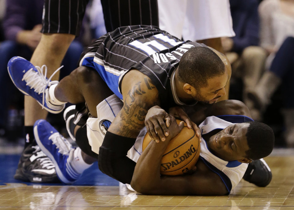 Dallas Mavericks' Darren Collison, bottom, and Orlando Magic guard Jameer Nelson, top, wrestle for control of a loose ball in the second half of an NBA basketball game Wednesday, Feb. 20, 2013, in Dallas. Nelson later left the game with a left leg injury. The Mavericks won 111-96. (AP Photo/Tony Gutierrez)