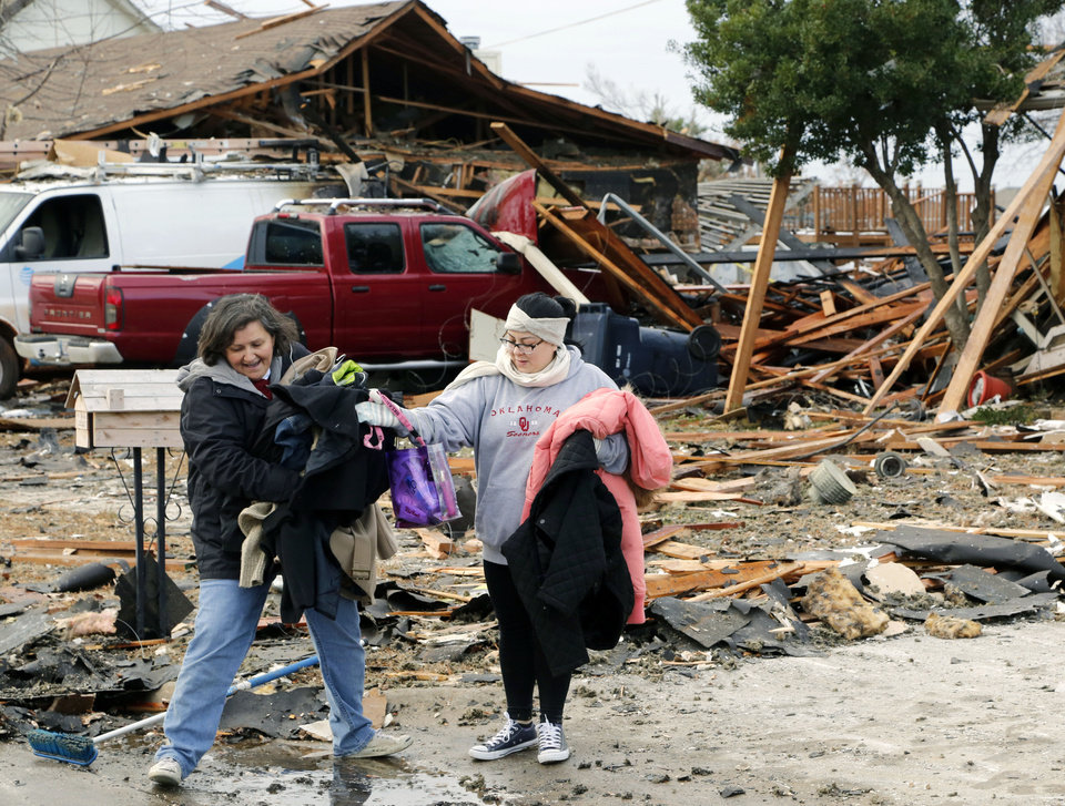 Photo - Stephanie Newman, left, and Bethany Partain, friends of a next-door neighbor to a house which exploded at 12409 Whispering Hollow Drive in Oklahoma City, OK, help remove belongings, Saturday, January 2, 2016. The cause of the explosion is being investigated. Photo by Paul Hellstern, The Oklahoman