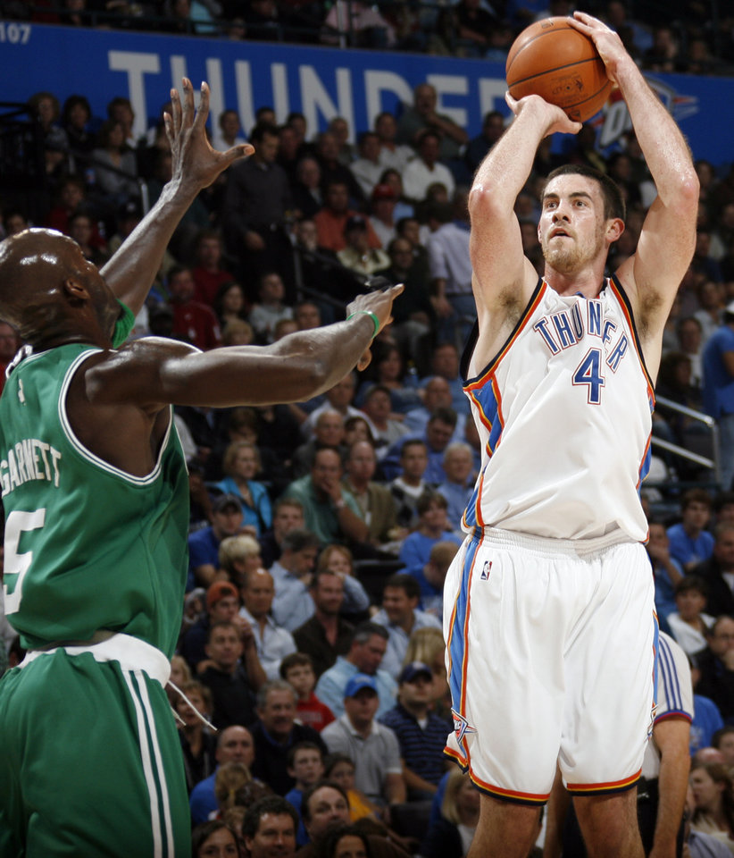 Photo - Nick Collison of the Thunder shoots the ball past Kevin Garnett of the Celtics in the first half during the NBA basketball game between the Oklahoma City Thunder and the Boston Celtics at the Ford Center in Oklahoma City, Wednesday, Nov. 5, 2008. BY NATE BILLINGS, THE OKLAHOMAN