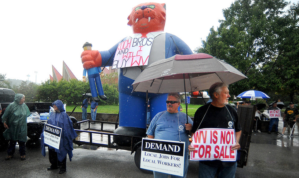 Photo - Protesters stand oustide in the rain as Former Massachusetts Gov. Mitt Romney speaks at Tamarack during the Working for Jobs Rally in Beckley, W.Va., Tuesday, Aug. 19, 2014. (AP Photo/Chris Tilley)
