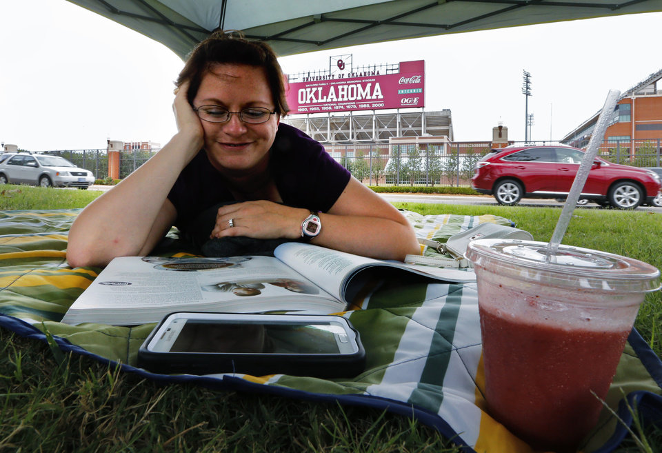 Photo -  Valerie Cook, of Houston, takes it easy Friday after claiming her tailgating spot across from Gaylord Family — Oklahoma Memorial Stadium. Photo by Steve Sisney, The Oklahoman   Steve Sisney -  STEVE SISNEY