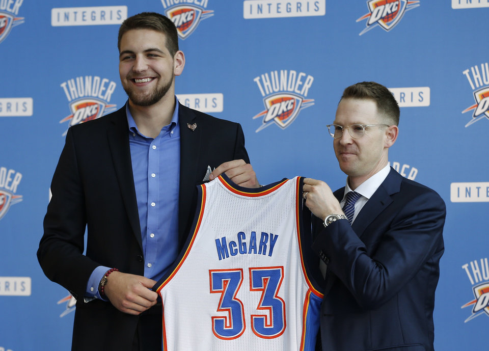 Oklahoma City Thunder forward Mitch McGary, left, and Thunder Executive Vice President and General Manager Sam Presti, right, hold a basketball jersey as McGary is introduced during a news conference in Oklahoma City, Friday, June 27, 2014. (AP Photo/Sue Ogrocki)