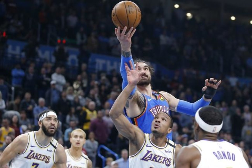 Photo -  Oklahoma City's Steven Adams (12) reaches for the ball over Los Angeles' Avery Bradley (11) during an NBA basketball game between the Oklahoma City Thunder and Los Angeles Lakers at Chesapeake Energy Arena in Oklahoma City, Saturday, Jan. 11, 2020. [Bryan Terry/The Oklahoman]