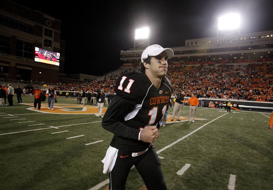 Photo - OSU's Zac Robinson (11) runs off the field following the college football game between Oklahoma State University (OSU) and the University of Colorado (CU) at Boone Pickens Stadium in Stillwater, Okla., Thursday, Nov. 19, 2009. Photo by Sarah Phipps, The Oklahoman