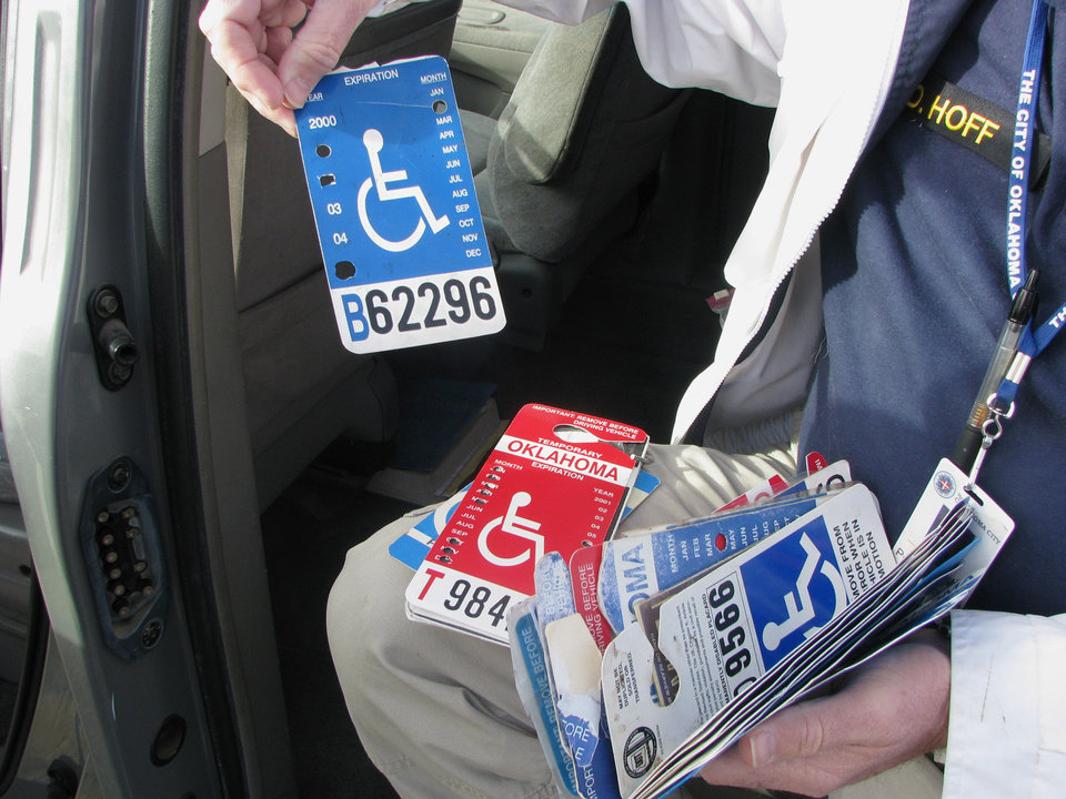 Photo - Handicap Parking Enforcement Specialist officer David Hoff holds bogus handicap parking placards he has confiscated. BY VALLERY BROWN, THE OKLAHOMAN