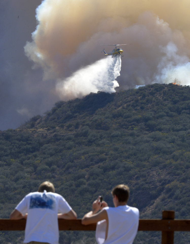 Photo - Residents watch a a helicopter drop water during a wildfire that burned several thousand acres, Thursday, May 2, 2013, in Ventura County, Calif.   (AP Photo/Mark J. Terrill)