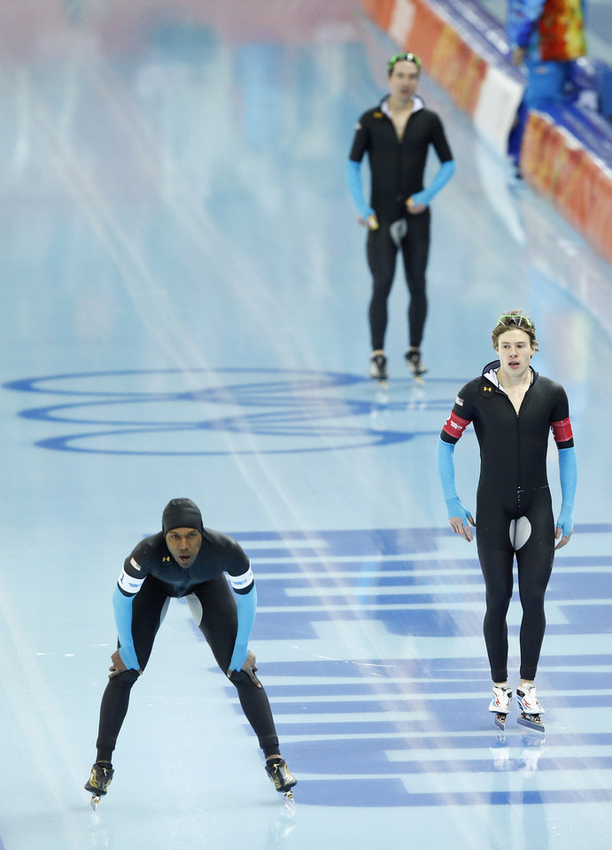 Photo - The U.S. speedskating team Shani Davis, left, Brian Hansen, right, and Jonathan Kuck, top, catch their breath after competing in the men's speedskating team pursuit quarterfinals at the Adler Arena Skating Center during the 2014 Winter Olympics in Sochi, Russia, Friday, Feb. 21, 2014. (AP Photo/Patrick Semansky)