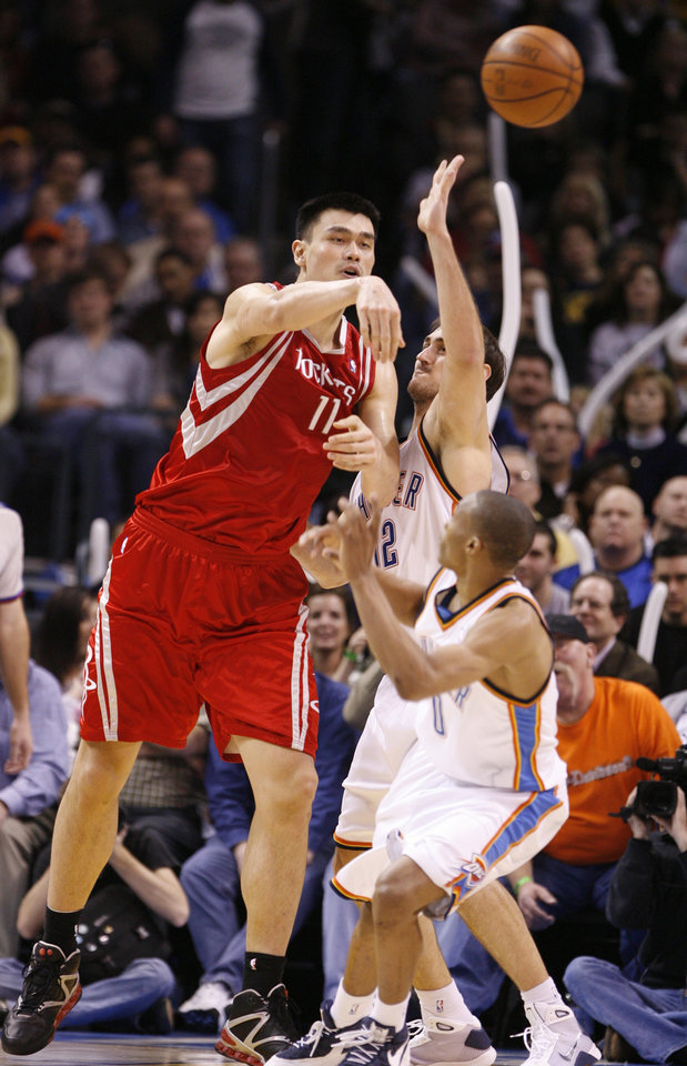 Photo - Yar Ming passes over Nenad Krstic and Russell Westbrook in the second half as the Oklahoma City Thunder plays the Houston Rockets at the Ford Center in Oklahoma City, Okla. on Friday, January 9, 2009. 