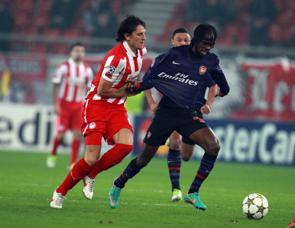 Photo - Olympiakos' Ljubomir Fejsa, left, fights for the ball with Arsenal's Gervinho, right, during a group B Champions League soccer match in the port of Piraeus, near Athens, Tuesday, Dec. 4, 2012. (AP Photo/Thanassis Stavrakis)