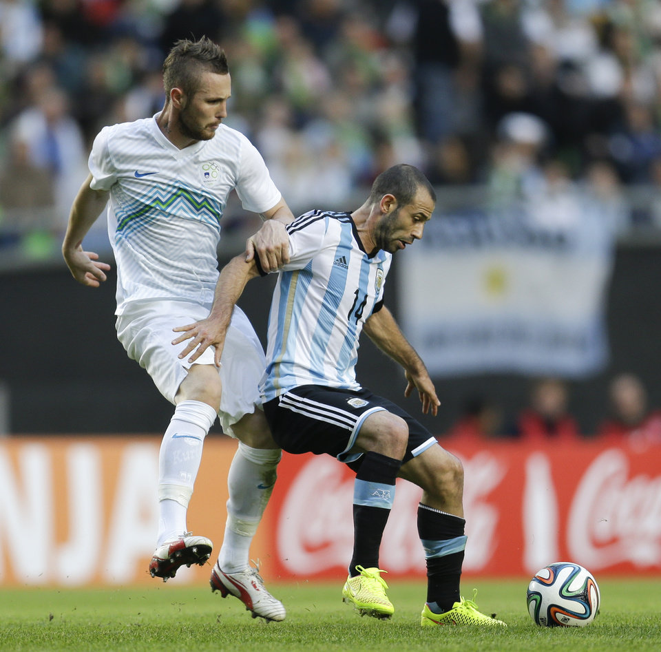 Photo - Argentina's Javier Mascherano, right, fights for the ball with Slovenia's Jasmin Kurtic during their international friendly soccer match in La Plata, Argentina, Saturday, June 7, 2014. Argentina's team is leaving June 9 for Brazil to compete at the World Cup. (AP Photo/Natacha Pisarenko)