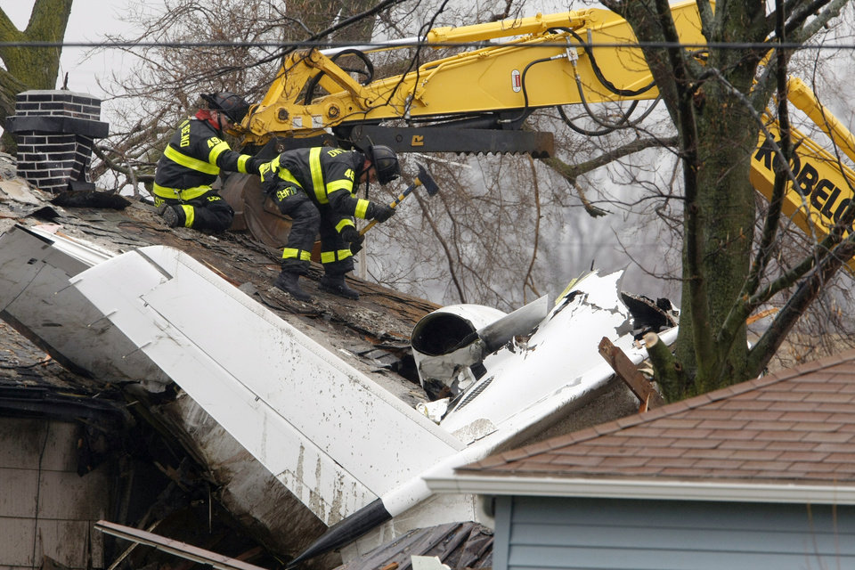 Photo - South Bend firefighters use an ax Monday, March 18, 2013, along Iowa Street in South Bend, Ind., as they prepare to remove a part of the roof of a home hit by a jet on Sunday. Two people were killed. (AP Photo/South Bend Tribune, James Brosher)