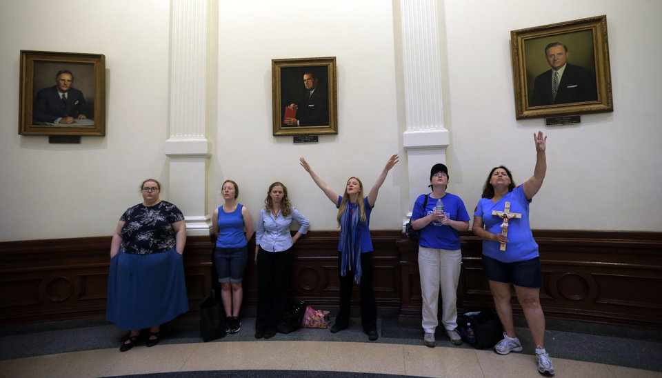 Photo - Anti-abortion supporters sing in the rotunda of the Texas Capitol as the Texas House  debates HB 2, a bill that will place restrictions on abortion in the state, Tuesday, July 9, 2013, in Austin, Texas. (AP Photo/Eric Gay)