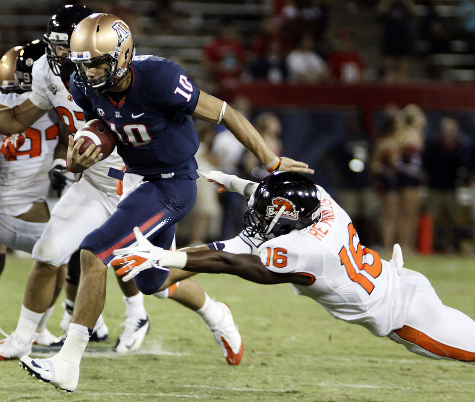 Arizona quarterback Matt Scott (10) evades a tackle by Oregon State\'s Rashaad Reynolds (16) during the second half of an NCAA college football game at Arizona Stadium in Tucson, Ariz., Saturday, Sept. 29, 2012. Oregon State won 38 -35. (AP Photo/Wily Low)
