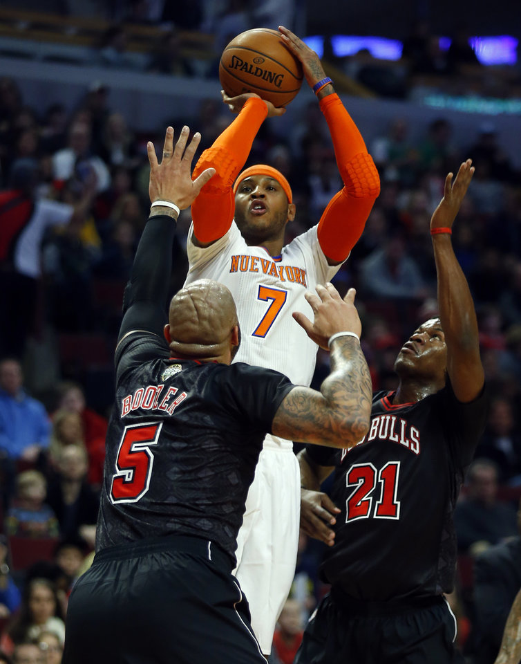 Photo - New York Knicks small forward Carmelo Anthony (7) shoots over Chicago Bulls forwards Carlos Boozer (5) and Jimmy Butler (21) during the first half of an NBA basketball game on Sunday, March 2, 2014, in Chicago. (AP Photo/Jeff Haynes)