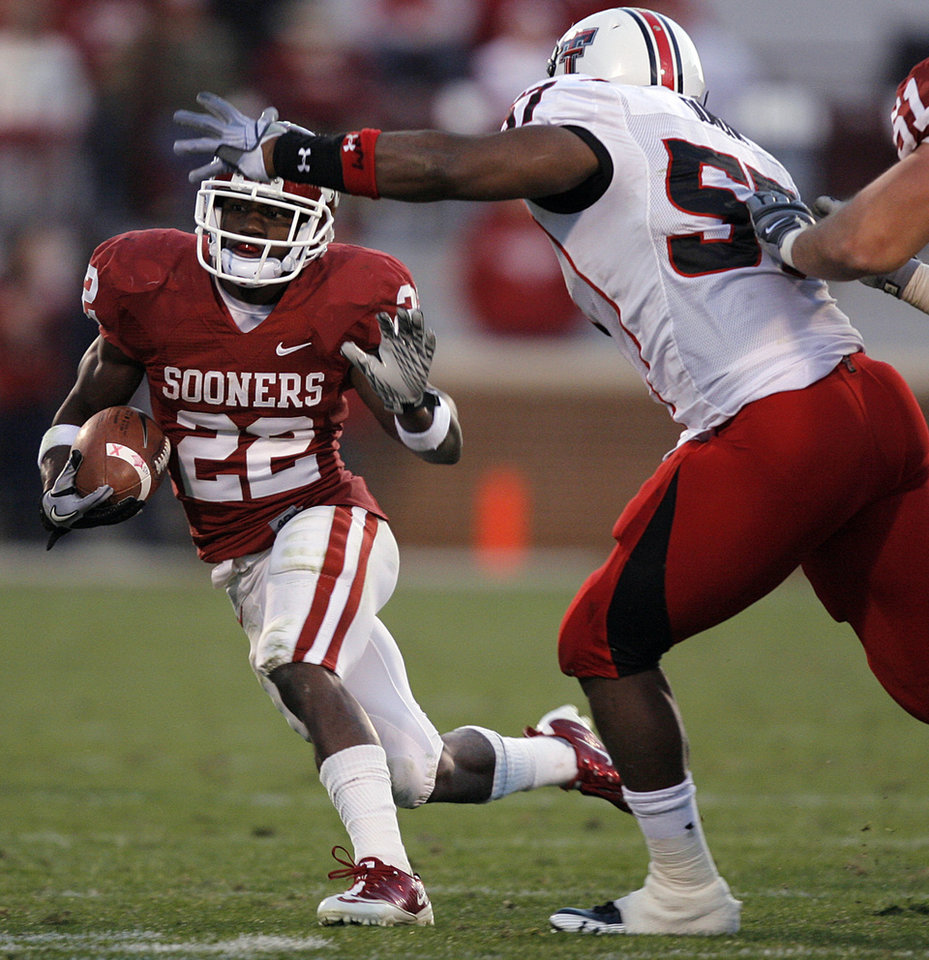 Photo - Oklahoma's Roy Finch (22) tries to get past Texas Tech's Brian Duncan (57) during the second half of the college football game between the University of Oklahoma Sooners (OU) and the Texas Tech Red Raiders (TTU) at the Gaylord Family Memorial Stadium on Saturday, Nov. 13, 2010, in Norman, Okla.  Photo by Chris Landsberger, The Oklahoman