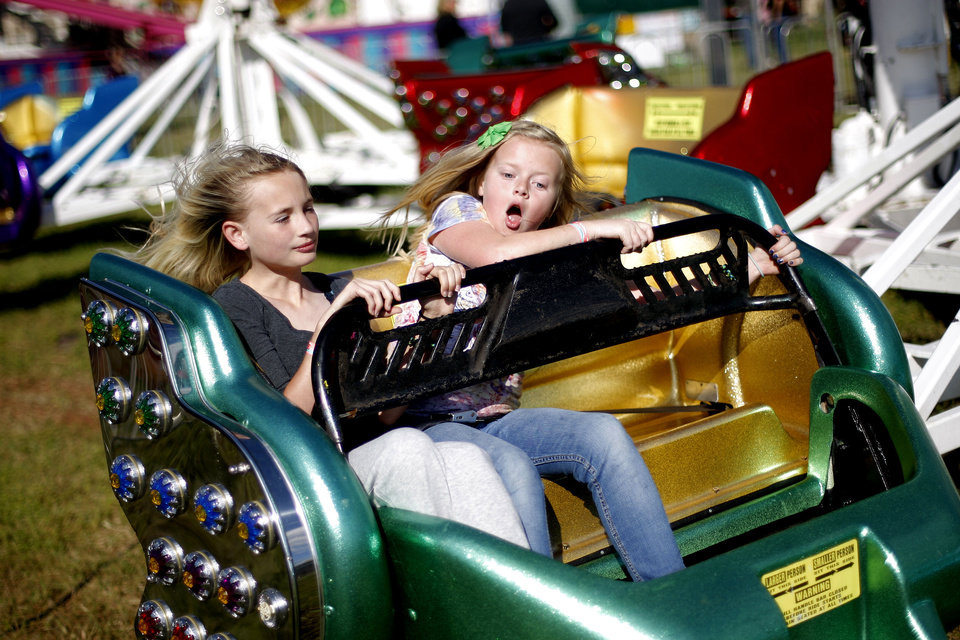 Photo - CHILD / CHILDREN / KIDS: Katie Pollard , 11, left, Emma Chesnut, 10, react as they hold on during a ride at the Guthrie 89er Day Celebration, Friday, April 20, 2012. Photo by Bryan Terry, The Oklahoman