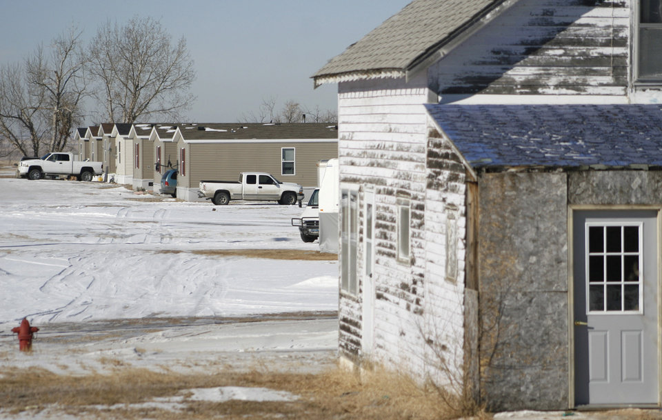 Photo - FILE - In this Feb. 27, 2014, file photo, new modular homes are seen behind an old house, right, in Grenora, N.D. The United States is still growing older, but the trend is reversing in the Great Plains, thanks to a liberal application of oil. (AP Photo/Martha Irvine, File)