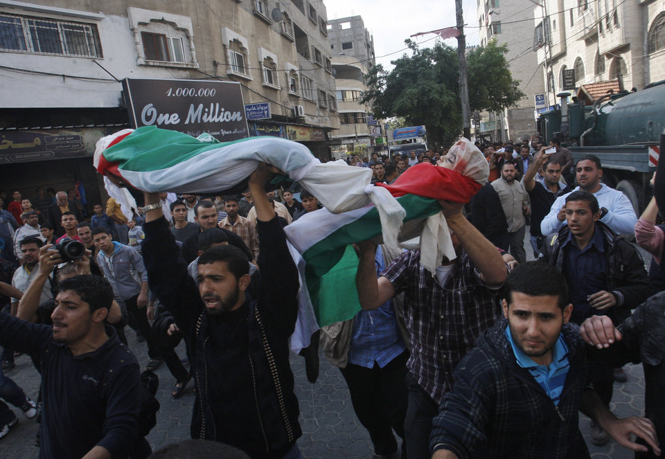 Photo -   Palestinians carry the bodies of members of the Daloo family during their funeral in Gaza City, Monday, Nov. 19, 2012. At least eleven members of the Daloo family were killed on Sunday when an Israeli missile struck the two-story home of the family in a residential area of Gaza City. (AP Photo/Hatem Moussa)