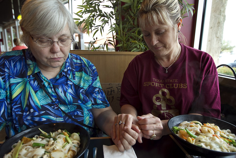 Photo -   ADVANCE FOR SUNDAY APRIL 1 - In this March 7, 2012 photo, Darylann Torrico, right, and Lynn Goodman-Strauss, of Mary House, hold hands and say grace before having lunch in Austin, Texas. (AP Photo/Austin American-Statesman, Rodolfo Gonzalez) MAGS OUT; NO SALES; INTERNET AND TV MUST CREDIT PHOTOGRAPHER AND STATESMAN.COM