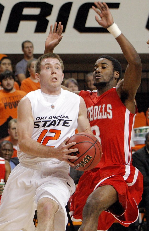 Photo - OSU's Keiton Page (12) takes the ball past Bryan Hammond (3) of Nicholls State in the first half during the men's college basketball game between Nicholls State University and Oklahoma State University at Gallagher-Iba Arena in Stillwater, Okla., Saturday, Nov. 21, 2010. Photo by Nate Billings, The Oklahoman