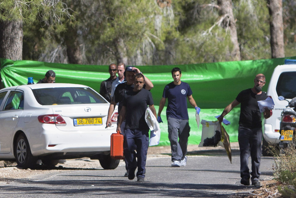 Israeli forensic police officers carry evidence bags in a forest in Jerusalem, Wednesday, July 2, 2014. Israeli police say Palestinians and Israeli forces have clashed following reports that an Arab teen was kidnapped and a body was found in a Jerusalem forest. Police spokesman Micky Rosenfeld said police received reports Wednesday that an Arab teen was forced into a car. A body was later found, but police have not yet established whether the two incidents are related. (AP Photo/Sebastian Scheiner)