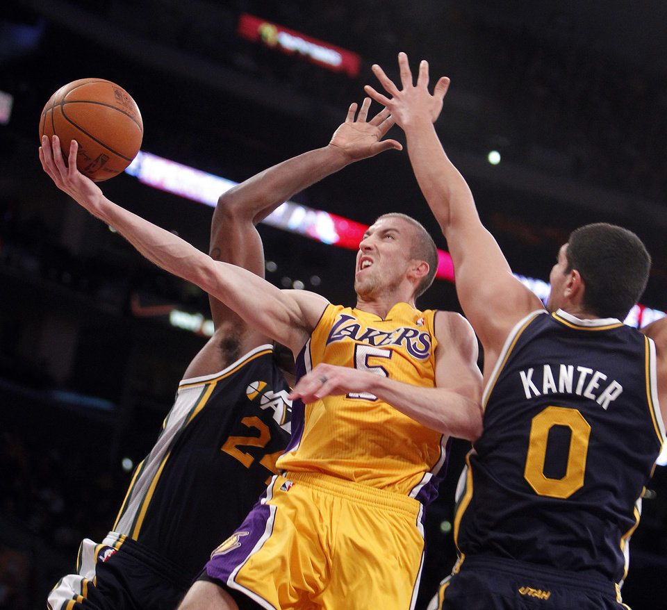 FILE - This Dec. 27, 2011 file photo shows Los Angeles Lakers guard Steve Blake, center, shooting between Utah Jazz forwards Paul Millsap, left, and Enes Kanter (0), of Turkey, during the second half of an NBA basketball game in Los Angeles. Blake and his wife have been attacked online since he missed a possible game-winning 3-pointer against the Oklahoma City Thunder in Game 2 of their Western Conference semifinal. (AP Photo/Alex Gallardo, File)