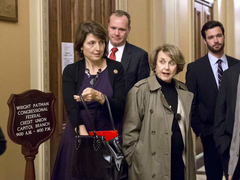 Photo - Rep. Cathy McMorris Rodgers, R-Wash., head of the Republican Conference, left, squeezes past Rep. Louise Slaughter, D-N.Y., the top Democrat on the House Rules Committee, at the end of the night after  a planned vote in the House of Representatives collapsed, Tuesday, Oct. 15, 2013, at the Capitol in Washington. Time growing desperately short, House Republicans pushed for passage of legislation late Tuesday to prevent a threatened Treasury default, end a 15-day partial government shutdown and extricate divided government from its latest brush with a full political meltdown.  (AP Photo/J. Scott Applewhite)