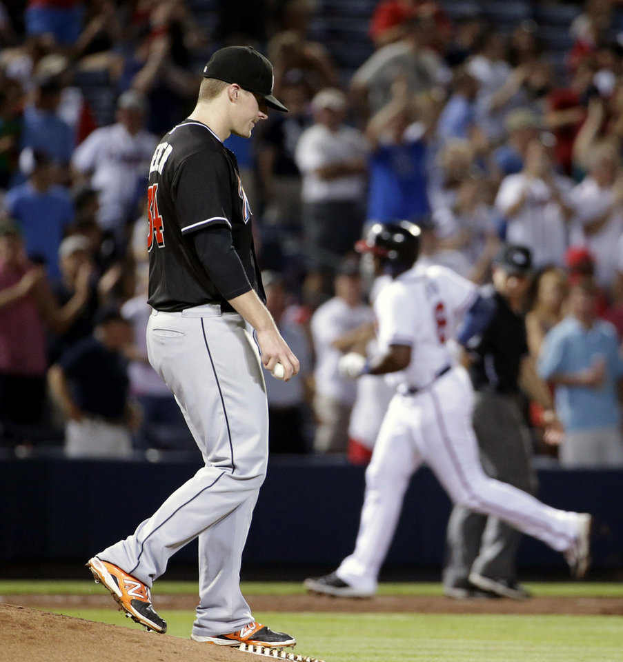Photo - Miami Marlins starting pitcher Tom Koehler, left, stands on the mound as Atlanta Braves' Justin Upton, right, rounds third base after hitting a two-run home run to score teammate Freddie Freeman in the sixth inning of a baseball game, Friday, Aug. 29, 2014, in Atlanta. (AP Photo/David Goldman)