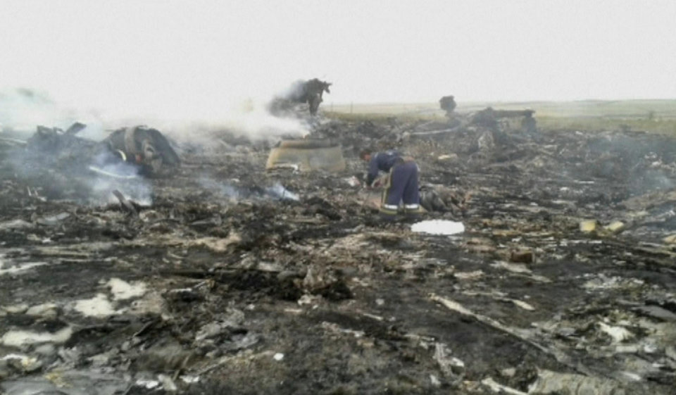 Photo - In this image taken from video, Thursday July 17, 2014,  people walk amongst the debris at the crash site after a passenger plane carrying 295 people was shot down Thursday as it flew over Ukraine, near the village of Hrabove, in eastern Ukraine. Malaysia Airlines tweeted that it lost contact with one of its flights as it was traveling from Amsterdam to Kuala Lumpur over Ukrainian airspace. (AP Photo / Channel 1) RUSSIA OUT - TV OUT