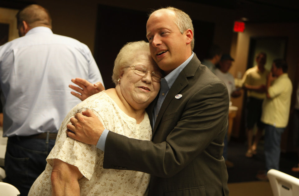 Photo - Brian Maughan (right), greets Glenda Hudson, of Oklahoma City, during a watch party for Brian Maughan, incumbent candidate for county commissioner, Tuesday, June 26, 2012.  Photo by Garett Fisbeck, The Oklahoman