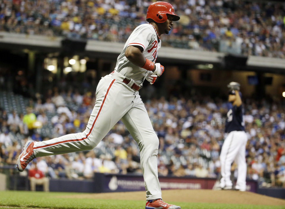 Photo - Philadelphia Phillies' Domonic Brown hits a home run off Milwaukee Brewers starting pitcher Wily Peralta during the third inning of a baseball game Tuesday, July 8, 2014, in Milwaukee. (AP Photo/Morry Gash)
