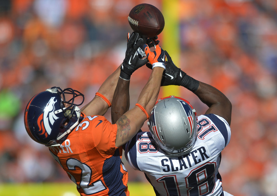 Photo - Denver Broncos cornerback Tony Carter (32) breaks up a pass intended for New England Patriots wide receiver Matthew Slater (18) during the first half of the AFC Championship NFL playoff football game in Denver, Sunday, Jan. 19, 2014. (AP Photo/Jack Dempsey)