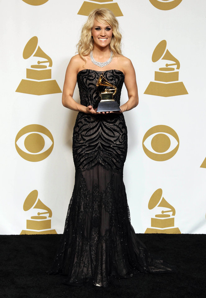 "Carrie Underwood poses backstage with the award for best country solo performance for ""Blown Away"" at the 55th annual Grammy Awards on Sunday, Feb. 10, 2013, in Los Angeles. (Photo by Matt Sayles/Invision/AP) ORG XMIT: CASH195"