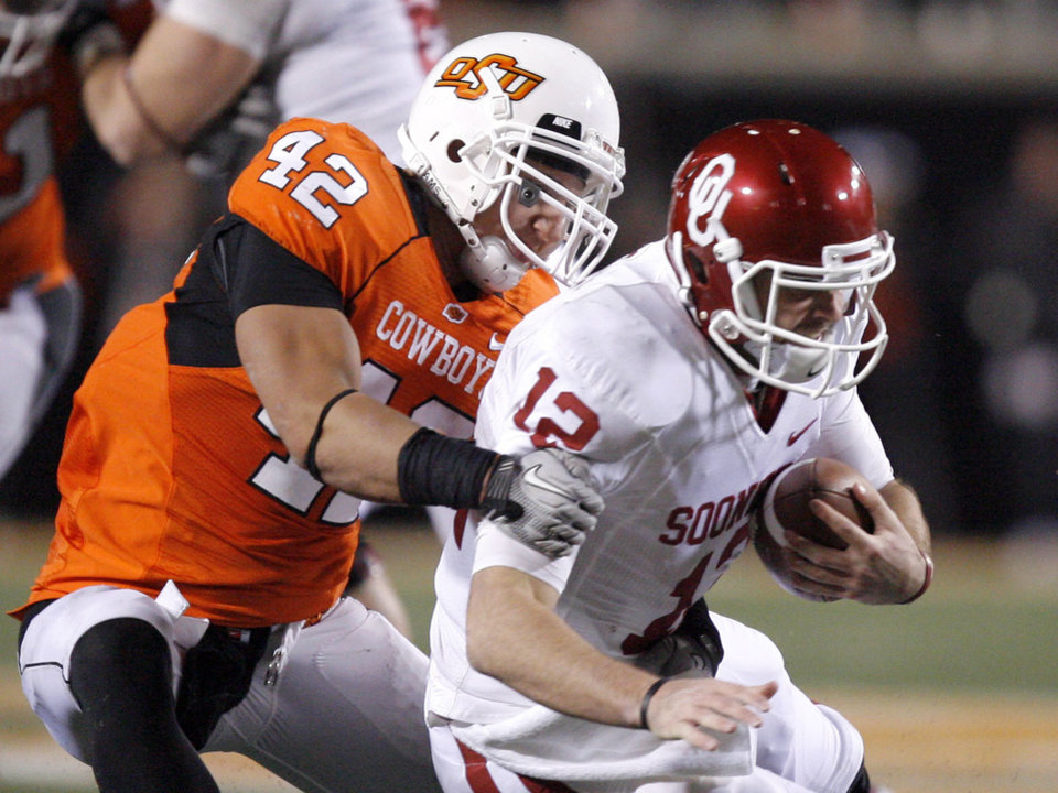 Photo - Oklahoma State's Justin Gent (42) sacks Oklahoma's Landry Jones  (12) during the Bedlam college football game between the University of Oklahoma Sooners (OU) and the Oklahoma State University Cowboys (OSU) at Boone Pickens Stadium in Stillwater, Okla., Saturday, Nov. 27, 2010. Photo by Sarah Phipps, The Oklahoman