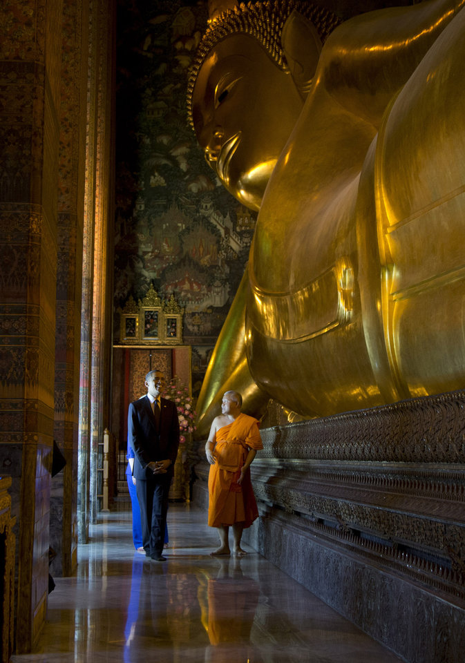 Photo -   U.S. President Barack Obama, front left, and U.S. Secretary of State Hillary Rodham Clinton, rear, tour the Viharn of the Reclining Buddha with Chaokun Suthee Thammanuwat, the Dean, Faculty of Buddhism Assistant to the Abbot of Wat Phra Chetuphon at the Wat Pho Royal Monastery in Bangkok, Thailand, Sunday, Nov. 18, 2012. (AP Photo/Carolyn Kaster)