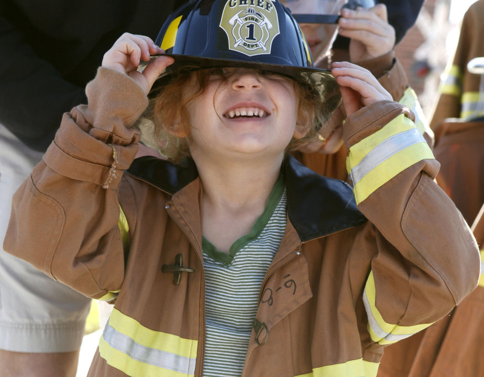 Four-year-old Aberly Lobato puts on a uniform, as the Edmond Fire Department holds its Children's Safety Challenge at the Children's Safety Village in Edmond, OK, Saturday, March 24, 2012,  By Paul Hellstern, The Oklahoman
