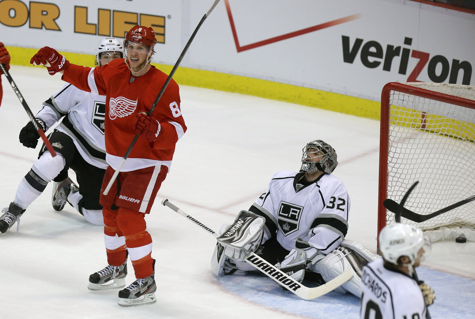 Photo - Los Angeles Kings goalie Jonathan Quick (32) looks up as Detroit Red Wings left wing Justin Abdelkader (8) celebrates the goal by teammate center Pavel Datsyuk during the second period of an NHL hockey game in Detroit, Wednesday, April 24, 2013. (AP Photo/Carlos Osorio)